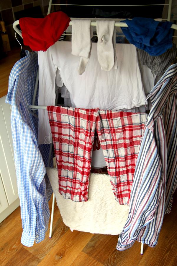 Domestic laundry, shirts, pajamas, socks, drying on an airer.  royalty free stock photos