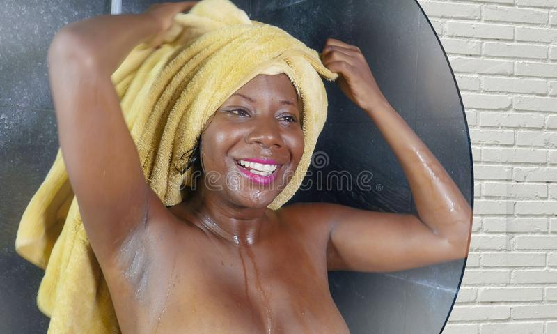 Domestic lifestyle mirror reflection portrait of young beautiful black afro American woman wet after having a shower with her head royalty free stock image