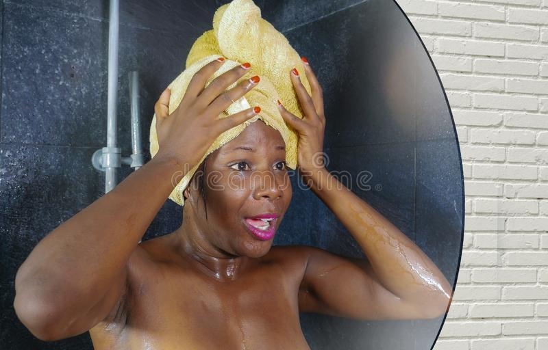 Domestic lifestyle mirror reflection portrait of young beautiful black afro American woman wet after having a shower with her head royalty free stock photos