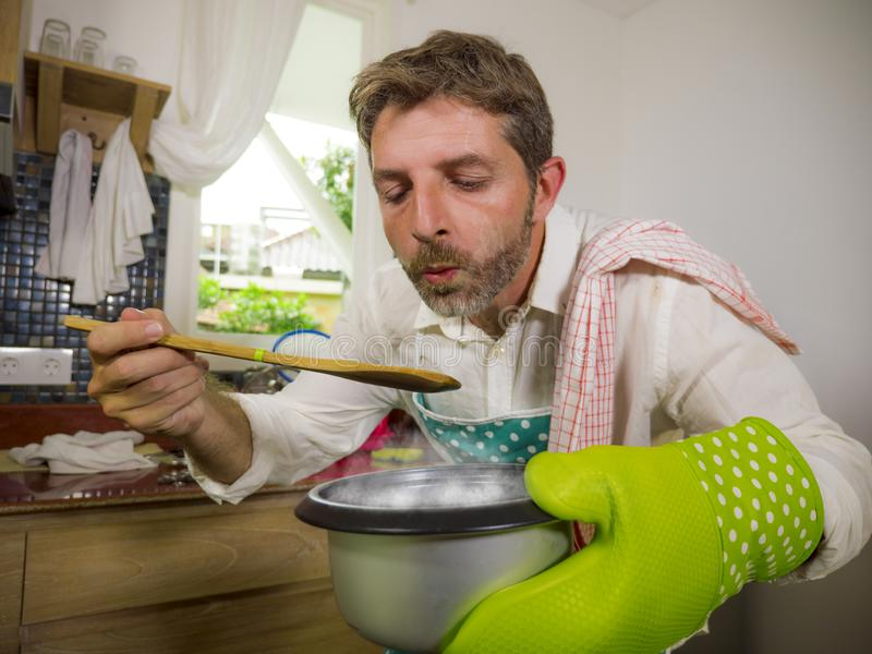 Domestic lifestyle portrait of happy and attractive man in apron and glove holding cooking pot tasting with spoon the delicious stock images