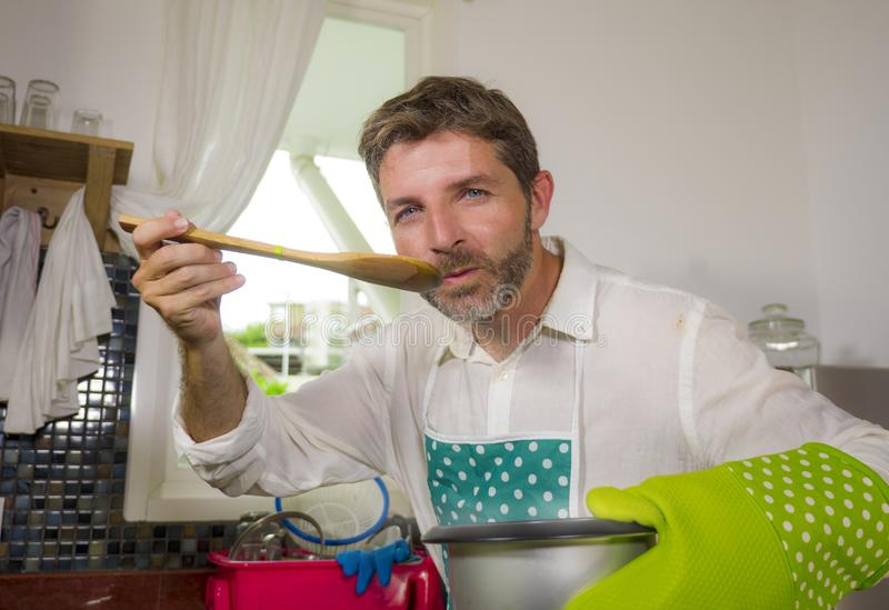 Domestic lifestyle portrait of happy and attractive man in apron and glove holding cooking pot tasting with spoon the delicious royalty free stock photo