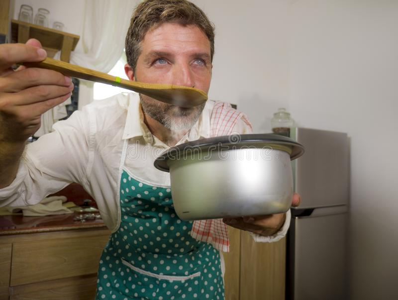 Domestic lifestyle portrait of happy and attractive man in apron holding steamy cooking pot tasting with spoon the delicious stock image
