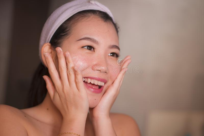 Domestic lifestyle portrait of young beautiful and happy Asian Chinese woman applying facial cosmetic cream smiling cheerful to royalty free stock photos