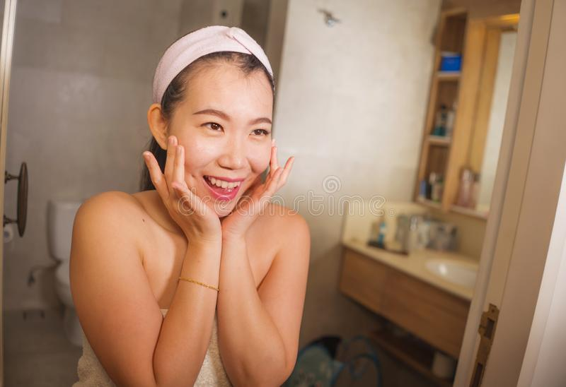 Domestic lifestyle portrait of young beautiful and happy Asian Chinese woman applying facial cosmetic cream smiling cheerful to royalty free stock photography