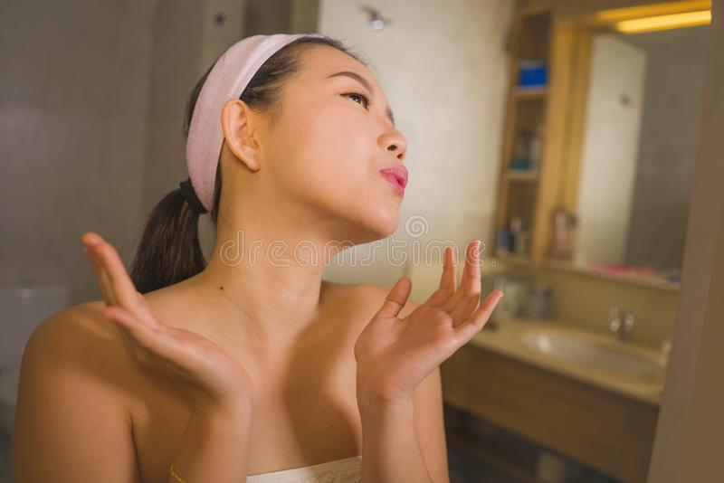Domestic lifestyle portrait of young beautiful and happy Asian Korean woman applying facial cosmetic cream smiling cheerful to stock images