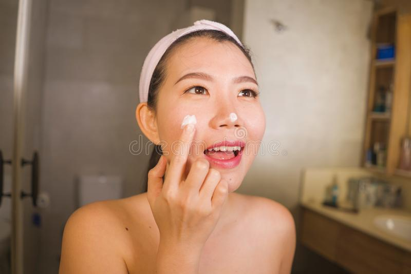 Domestic lifestyle portrait of young beautiful and happy Asian Korean woman applying facial cosmetic cream smiling playful to royalty free stock image