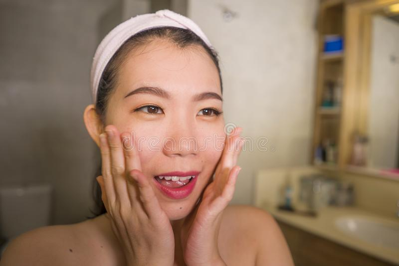 Domestic lifestyle portrait of young beautiful and happy Asian Korean woman applying facial cosmetic cream smiling playful to royalty free stock photo