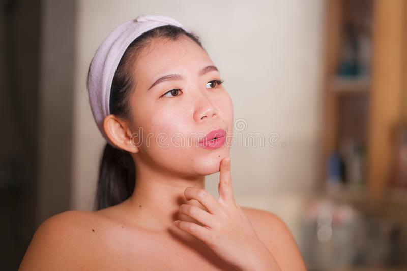 Domestic lifestyle portrait of young beautiful and happy Asian Korean woman applying facial cosmetic cream smiling playful to stock image