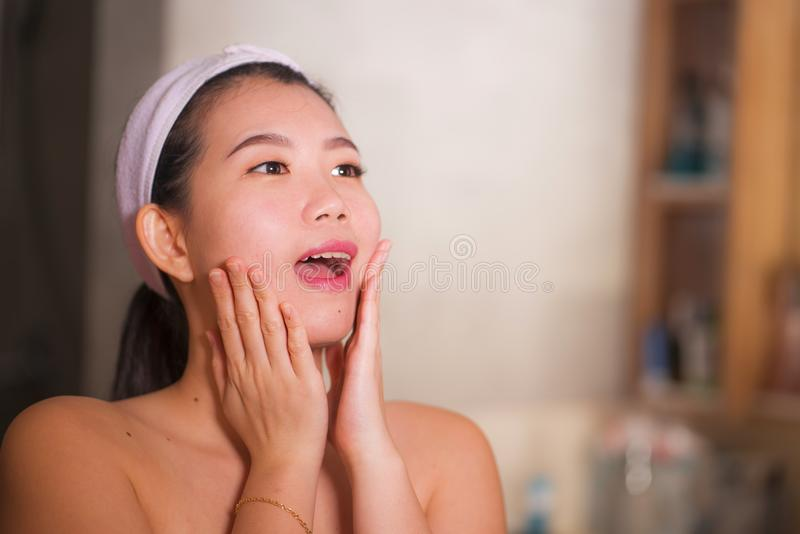 Domestic lifestyle portrait of young beautiful and happy Asian Korean woman applying facial cosmetic cream smiling playful to stock photography