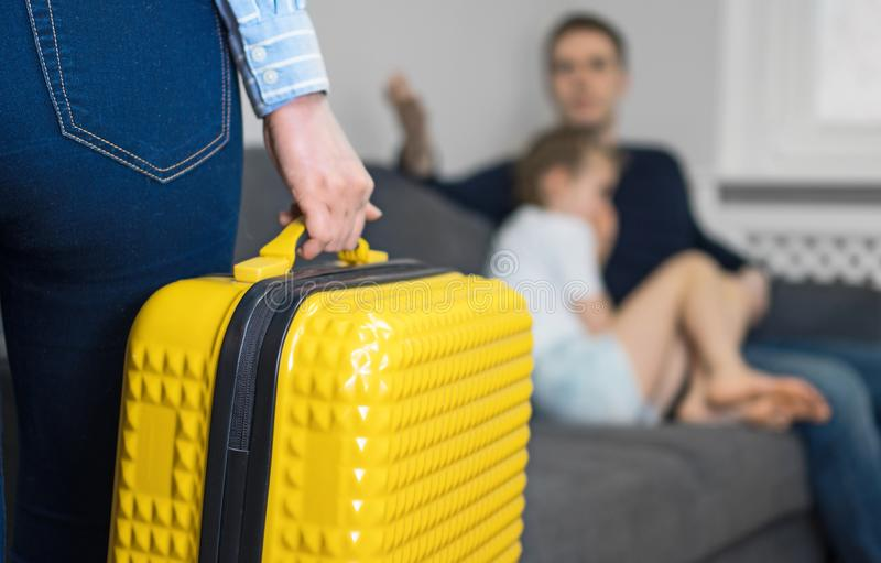 Domestic quarrel. Mother with suitcase leaving his family stock photos