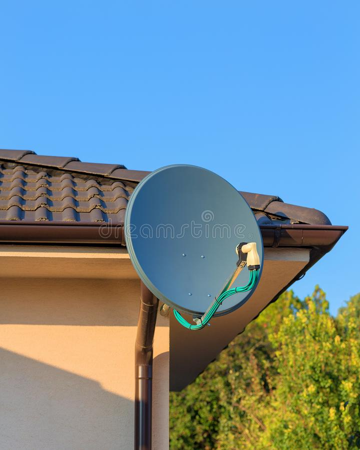 Domestic satellite tv installation under the eaves of home with octo monoblock converter. Residential TV receiver satellite dish royalty free stock photos