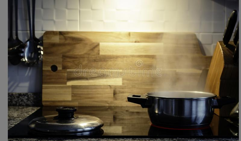 Domestic scene of a Steam oven cooking pot in a electric kitchen with a wood table on background.  royalty free stock photos