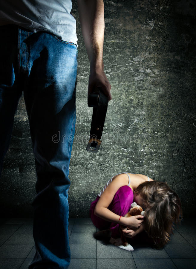 Domestic violence. Man with a belt standing over a litlle girl cowering on the floor stock image
