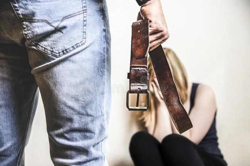 Domestic violence concept. Girl is abused by her angry stepfather with belt royalty free stock photography