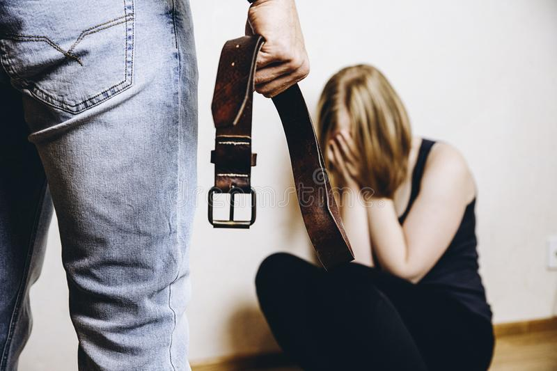 Domestic violence concept. Girl is abused by her angry stepfather with belt royalty free stock photos