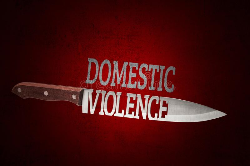 Domestic violence. Kitchen knife with blade of letters on dark red royalty free stock photography