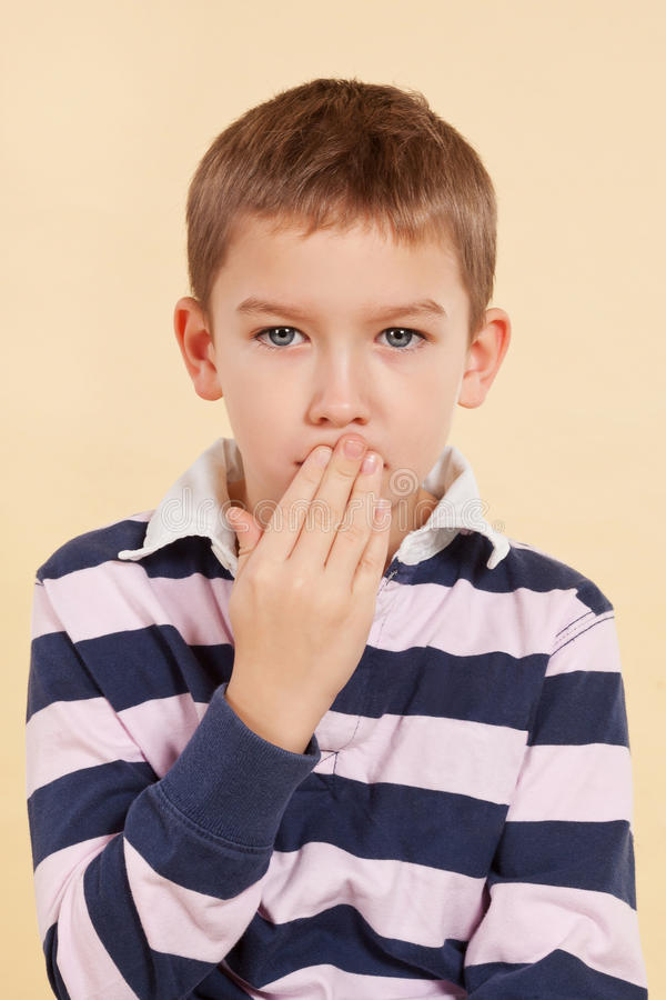Domestic violence. Psst. Young boy with hand over his mouth isolated. Domestic violence concept. Don't tell anyone. Psst stock images