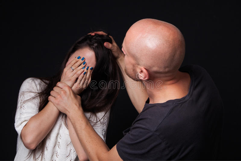 Domestic violence to woman. Domestic violence - men beating the woman, she is closing her face with hands, black background royalty free stock photos