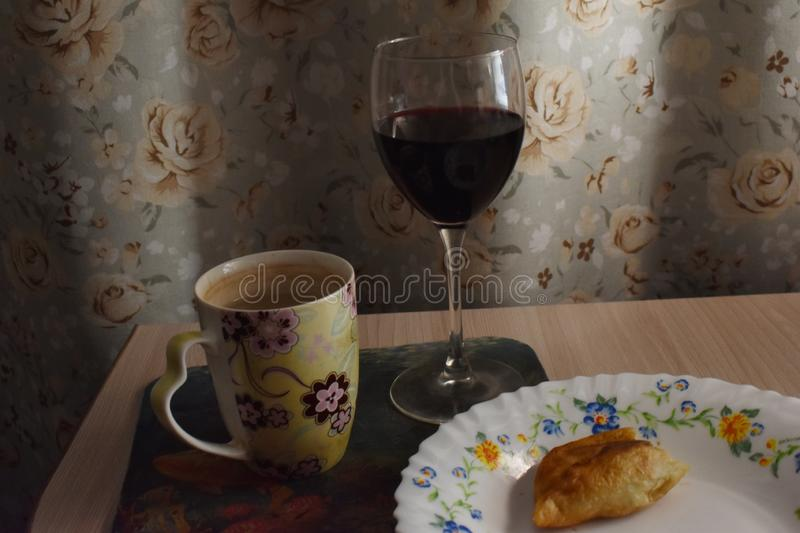 Domestic wine in the glass with a half-eaten pie. royalty free stock image