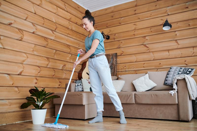 Domestic work. Pretty young housewife in casualwear cleaning floor in living-room while doing domestic work stock images