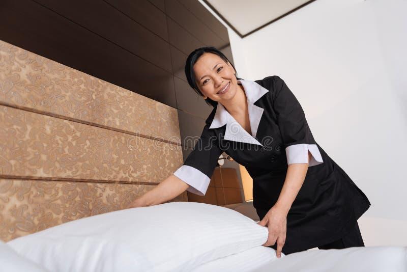 Domestique asiatique gaie d'hôtel faisant le service d'étage photos stock