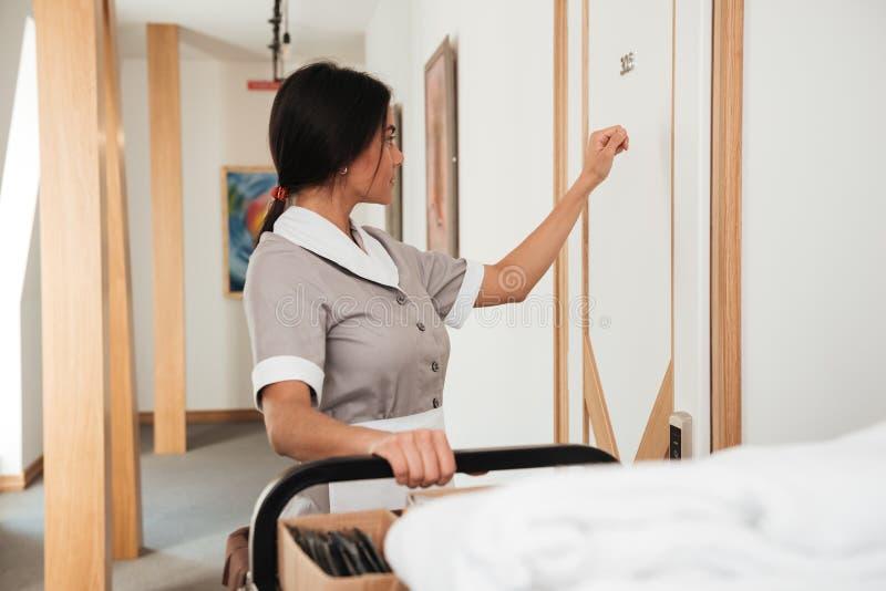 Domestique d'hôtel frappant sur la porte d'hôtel pour le service d'étage images libres de droits