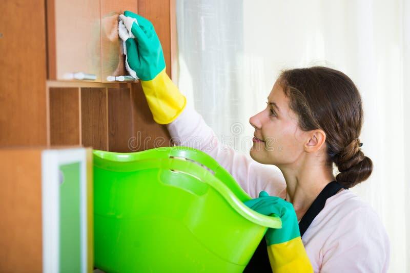 Domestique dans le saupoudrage et l'essuyage de tablier photographie stock