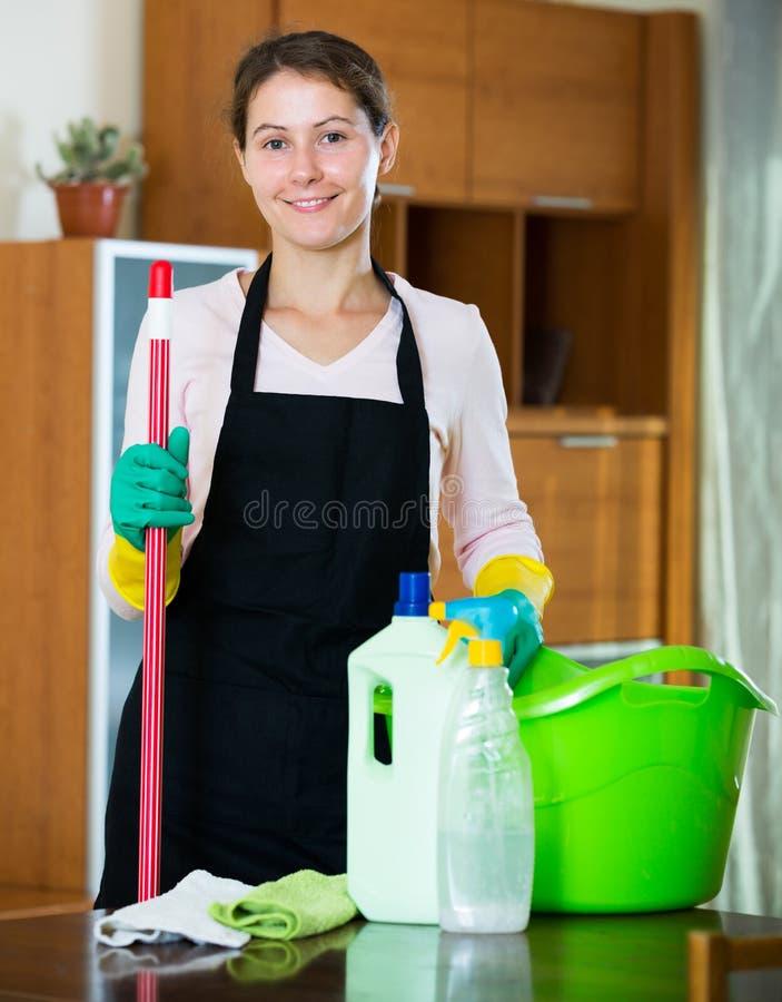 Domestique dans le saupoudrage et l'essuyage de tablier photos stock