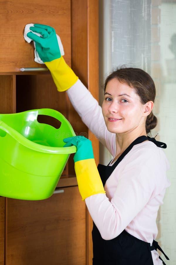 Domestique dans le saupoudrage et l'essuyage de tablier images stock
