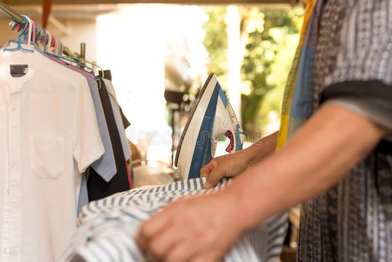Domestique de Chambre faisant les vêtements repassants photos stock