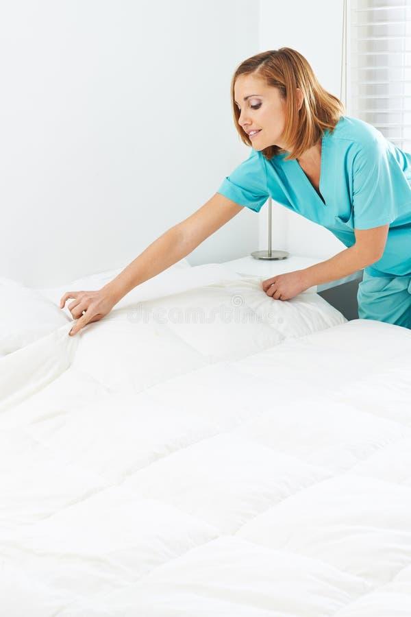 Domestique faisant les lits dans une maison de repos photo libre de droits