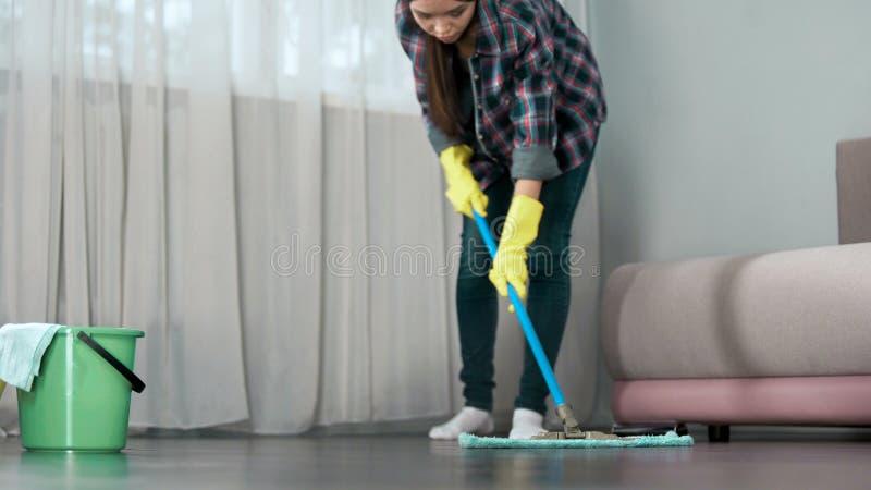Domestique lavant soigneusement le plancher de la chambre d'hôtel avant l'arrivée des invités, nettoyant photographie stock libre de droits