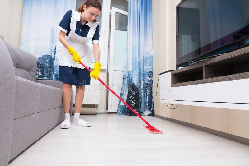 Domestique ou femme de charge nettoyant un salon photos libres de droits
