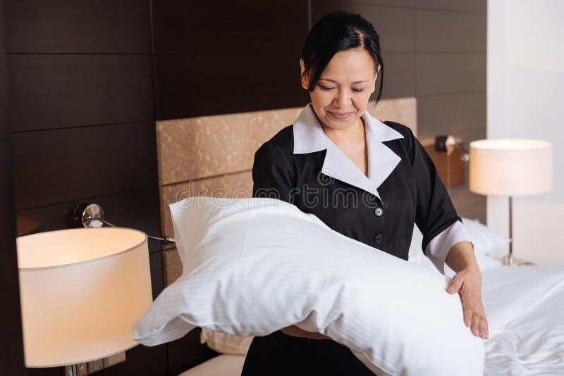 Domestique travaillante dure positive d'hôtel regardant l'oreiller images stock