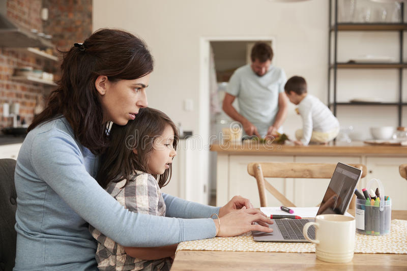 Domicilio familiar ocupado con el funcionamiento de la madre como padre Prepares Meal imágenes de archivo libres de regalías