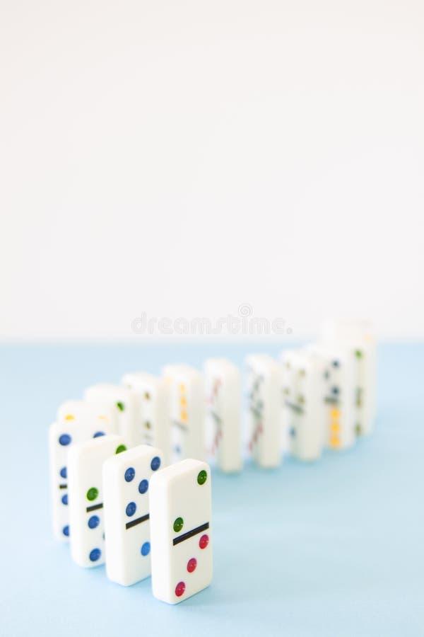 Dominós brancos com os pontos brilhantemente coloridos alinhados em uma série de encurvamento imagens de stock