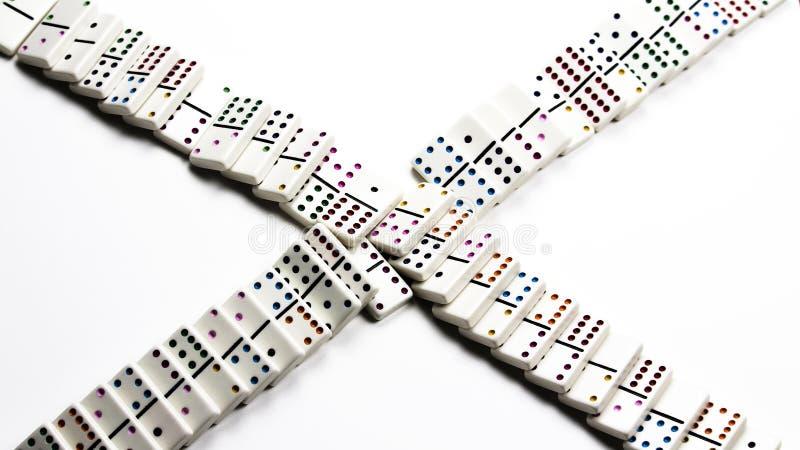 Dominós de cerámica blancos caidos en modelo de la travesía fotografía de archivo