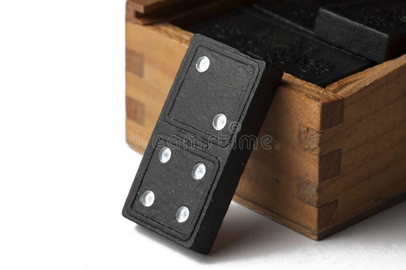 Domin?s negros en una caja de madera aislada en un fondo blanco Copie el espacio imágenes de archivo libres de regalías