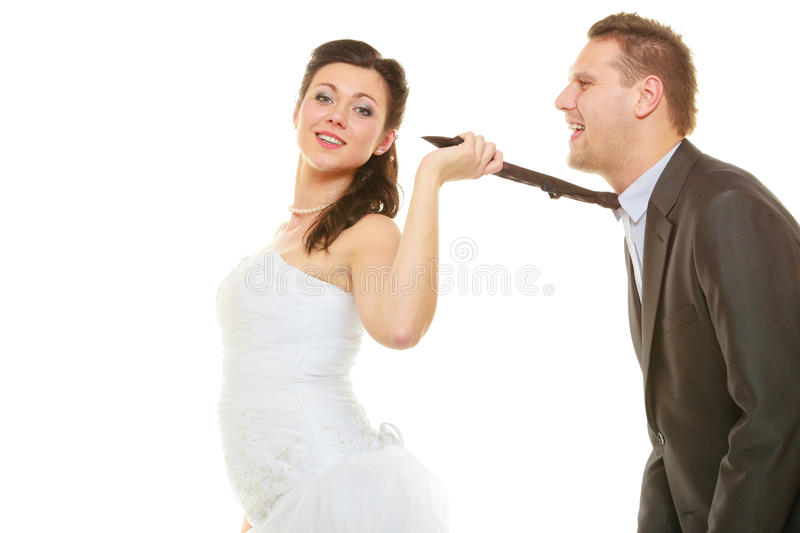 Dominant bride wearing wedding dress pulling groom tie stock image