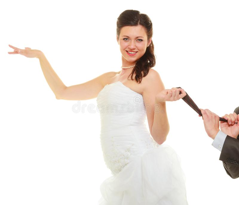 Dominant bride wearing wedding dress pulling groom tie royalty free stock photos