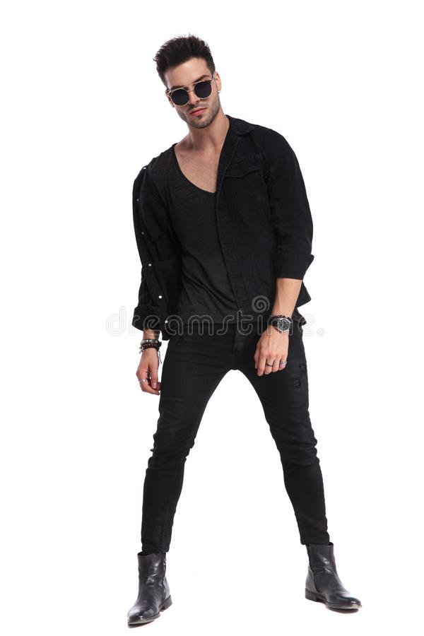 Dominant man in black clothes standing with legs parted. Dominant man in black clothes standing on white background with parted legs, full length picture stock images