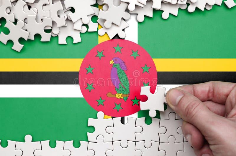 Dominica de vlag wordt afgeschilderd op een lijst waarop de menselijke hand een raadsel van witte kleur vouwt stock afbeelding