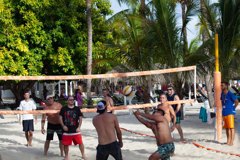 Group young friends playing volleyball on beach royalty free stock images