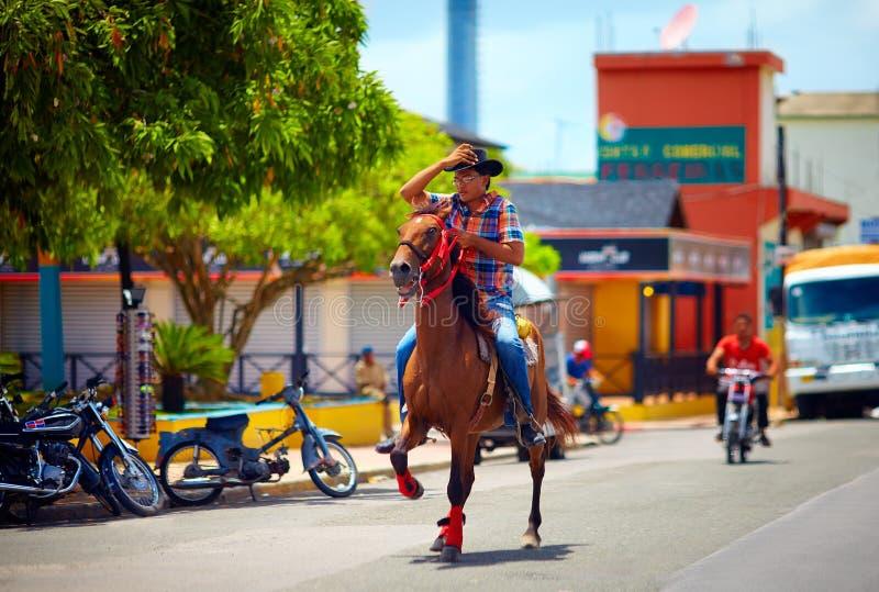 DOMINIKANISCHE REPUBLIK - 30. AUGUST 2015: Junger Cowboy, der ein Pferd auf die Stadtstraße reitet lizenzfreie stockbilder