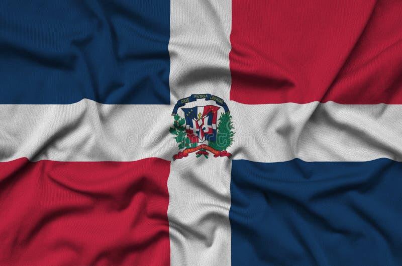 Dominikanska republikenflaggan visas på ett sporttorkduketyg med många veck Baner för sportlag royaltyfri fotografi