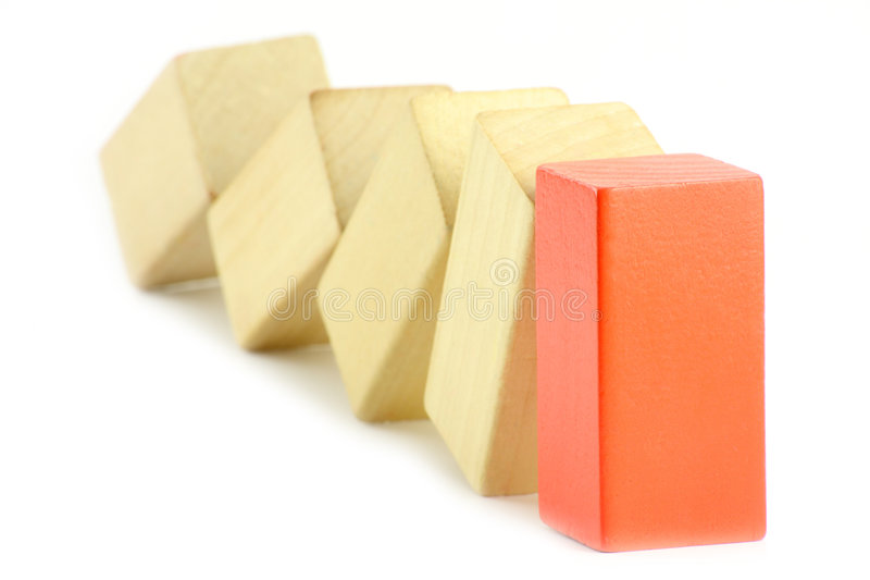 Domino of blocks. Domino of wooden blocks, one block red stock photography