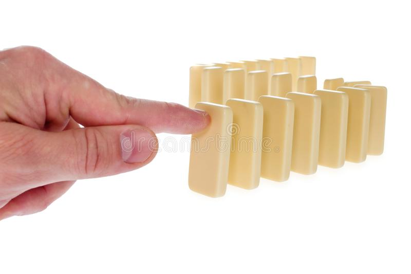 Domino in a creamy color arranged in a row pressed by a finger b stock images