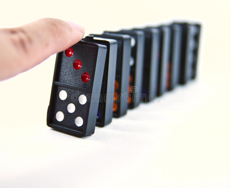 Domino effect. A finger ready to start domino chain reaction royalty free stock photo