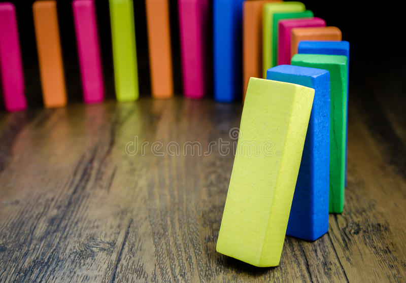 The domino effect of colorful wooden blocks. Selective focus royalty free stock image