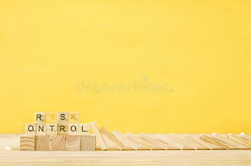 The domino effect hits wooden blocks with the text risk control. The domino effect hits wooden blocks with the text risk control royalty free stock photo